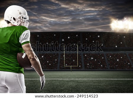 Football Player with a green uniform on a stadium. - stock photo