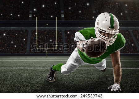 Football Player with a green uniform scoring on a Stadium. - stock photo
