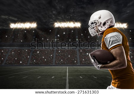 Football Player with a orange uniform running on a stadium. - stock photo
