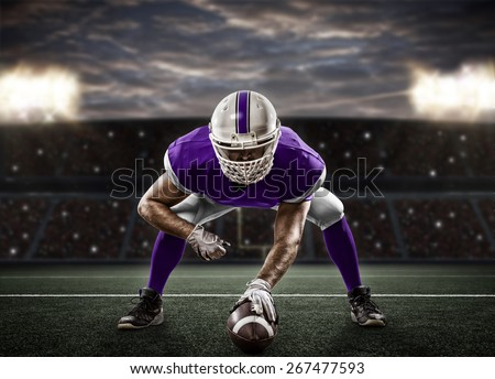 Football Player with a purple uniform on the scrimmage line, on a stadium. - stock photo