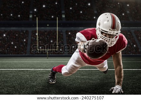 Football Player with a red uniform scoring on a Stadium. - stock photo