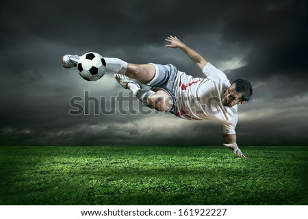 Football player with ball in action outdoors - stock photo