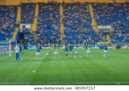 Football players on the field before the game generic background, intentionally blurred post production. 