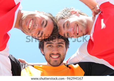 Football players put heads together - stock photo