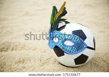 Football soccer ball wearing blue Brazilian carnival mask on beach in Rio de Janeiro - stock photo