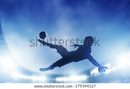 Football, soccer match. A player shooting on goal performing a bicycle kick. Lights on the stadium at night. - stock photo