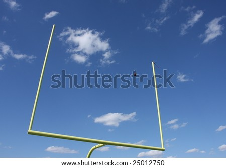 Football uprights with a ball kicked through - stock photo