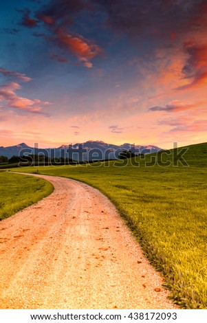 footpath and meadow with mountain kampenwand , evening sky - stock photo