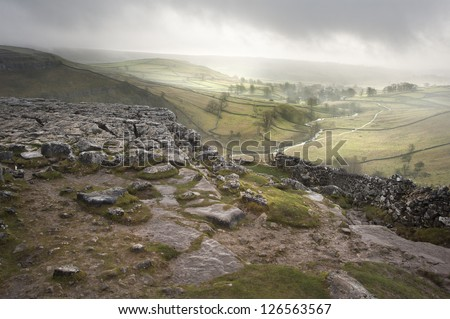Footpath from limestone pavement down to Malham Cove in Yorkshire Dales National Park during Autumn sunrise - stock photo