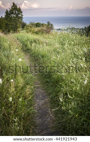 Footpath in grassy meadow along cliffs with view of big body of water. Lake Ontario, Canada. - stock photo