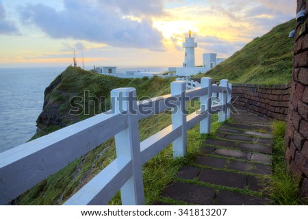 Footpath leading to a lighthouse on the cliff in northern coast of Taiwan with view of beautiful golden sunrise in the background - stock photo