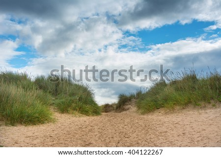 Footpath through sand dunes with blue sky ahead - stock photo