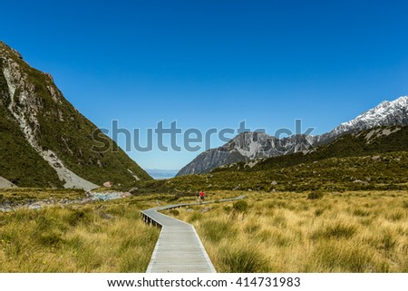 Footpath trail section in Hooker Valley with blue sky-Mount Cook, highest peak of Southern Alps, New Zealand - stock photo