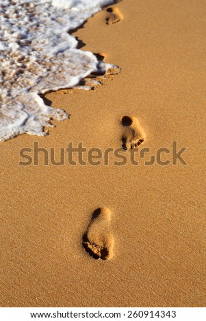 Footprint on pristine golden sandy beach and waterline - Portugal. ( Selective focus on first footprint.) - stock photo