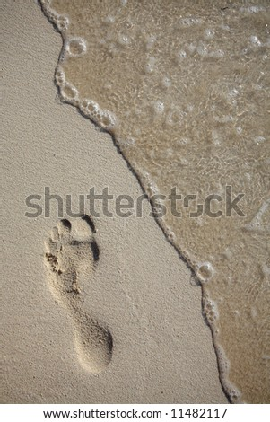 Footprint on sand beach with wave - stock photo