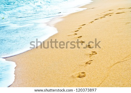 Footprint on sand with foam - stock photo