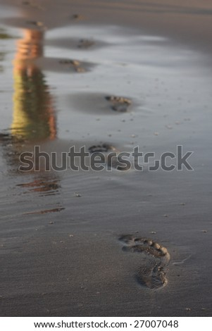 footprints and reflection on the wet sand - stock photo
