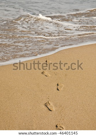 Footprints in sand heading to the water - stock photo