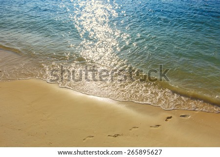 Footprints in sand on golden tropical beach in front of small wave rolling in. Sun highlights reflecting on ocean surface. - stock photo