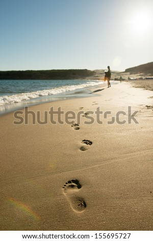 footprints in the sand at the beach - stock photo