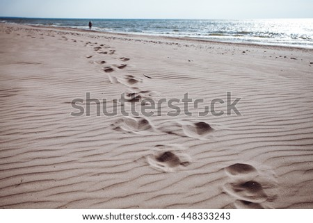 Footprints in the sand of the sea - stock photo