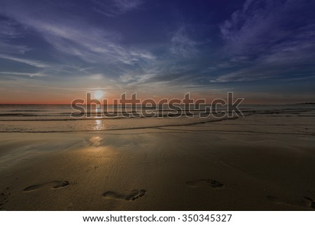 footprints in the sand waves in the sea coast sunset - stock photo