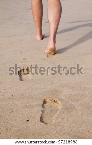 Footprints in wet sand in a line with a man walking on the beach - stock photo