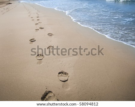 Footprints in wet sand of beach, Spain - stock photo