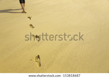 Footprints of a young woman walking on a soft sandy beach /footprints in sand - stock photo