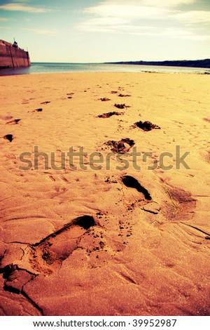 Footprints on a beach - stock photo