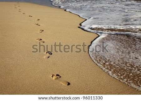 footprints on a sandy beach - stock photo
