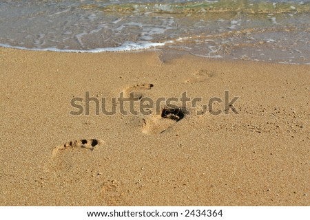 Footprints on a sandy beach heading for sea - stock photo