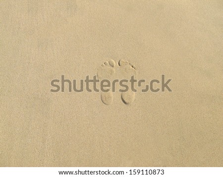 Footprints on beach - stock photo