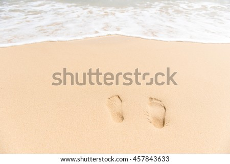 Footprints on sea shore. Sea water wave. Beach Vacation - stock photo