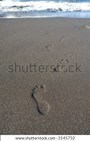 Footprints on the beach leading to the sea. - stock photo