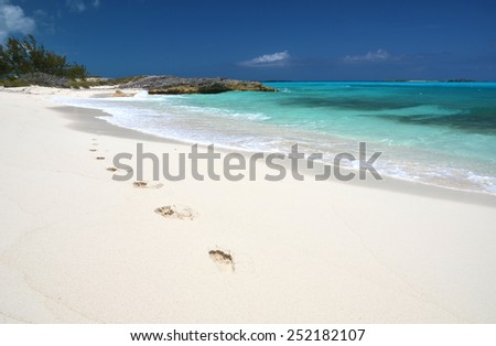Footprints on the desrt beach of Little Exuma, Bahamas - stock photo