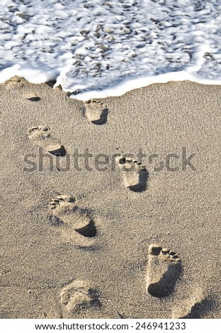 Footprints on the sand leading to the sea foam - stock photo