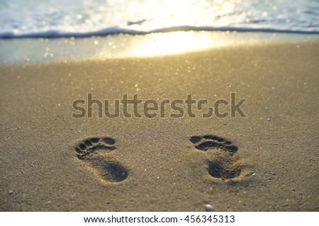Footprints on the sandy beach on a golden summer morning. - stock photo