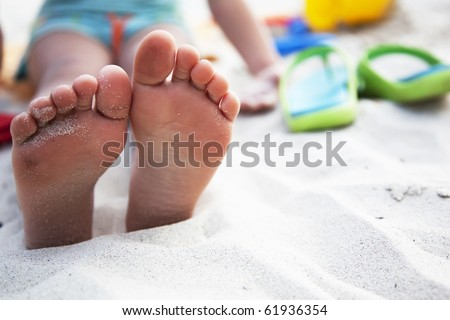 foots of little girl at the beach and slates nearby - stock photo