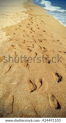 Footsteps in the sand at the beach - retro styled photo - stock photo