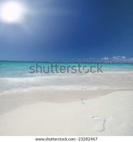 Footsteps on a Beautiful Caribbean tropical beach with white sand and green ocean, suitable background for a variety of designs - stock photo