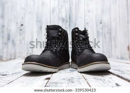 Footwear concept. Men's winter boots of black colour isolated on white wooden background. A pair of boots represented one near another. - stock photo