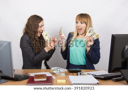 for office table two women collaborators happily hold hands in a pack with the money and express strong - stock photo