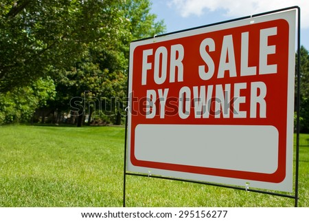For Sale By Owner Sign. Picture of a For Sale By Owner sign in a yard. Has copy space for adding text. - stock photo