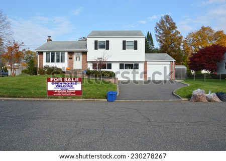 For Sale Open House Welcome Real Estate sign blue recycle bin bagged leaves suburban high ranch style home residential neighborhood fall season blue sky clouds USA - stock photo