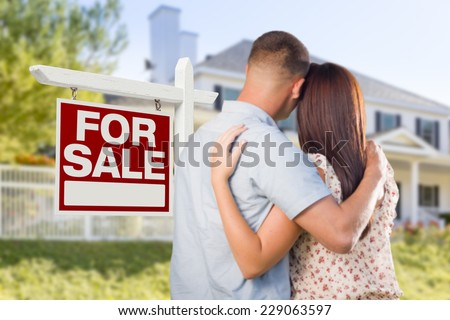 For Sale Real Estate Sign and Affectionate Military Couple Looking at Nice New House. - stock photo