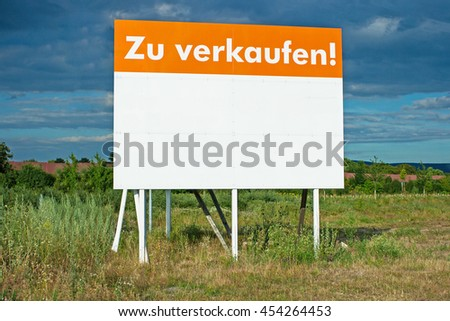For Sale text  in German. Huge billboard for land sale  to build a house or manufacture on green grass background - stock photo