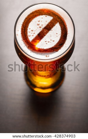 forbidden symbol on foam in beer glass on black table, view from above - stock photo