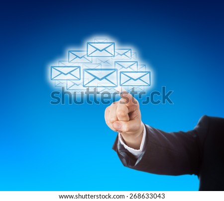 Forearm in blue corporate suit is reaching out to touch a swarm of emails in the shape of a cloud. Business or technology metaphor for mobile computing and instant information access. Copy space. - stock photo