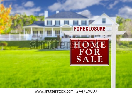 Foreclosure Home For Sale Real Estate Sign in Front of Beautiful Majestic House. - stock photo